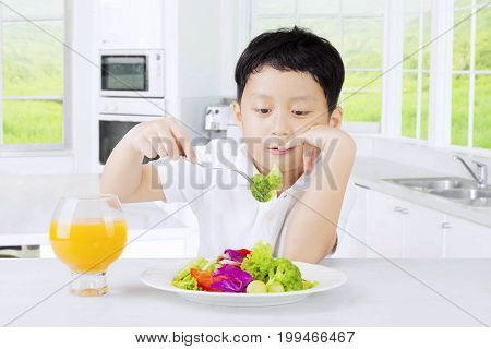 Cute boy tasting a plate vegetables salad and looks bored shot in the kitchen at home
