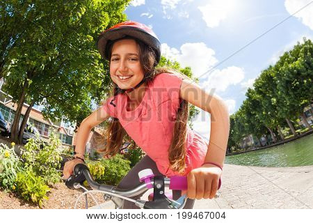 Happy preteen girl in helmet riding her bike along the river embankment and looking at camera