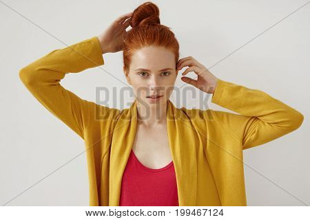 Confident Female With Red Hair Bun, Freckled Healthy Skin And Green Eyes, Keeping Her Hands On Head,