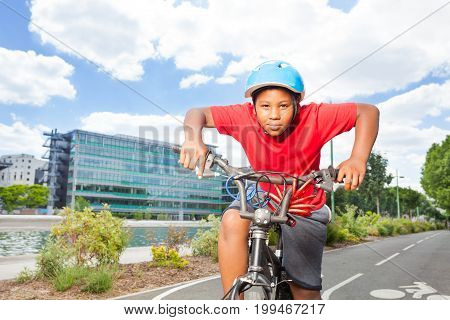 Portrait of preteen African boy in safety helmet riding his bike on cycle path in summer