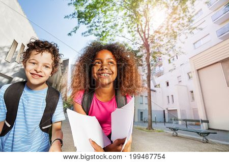Two school children, Caucasian boy and African girl holding papers looking at camera