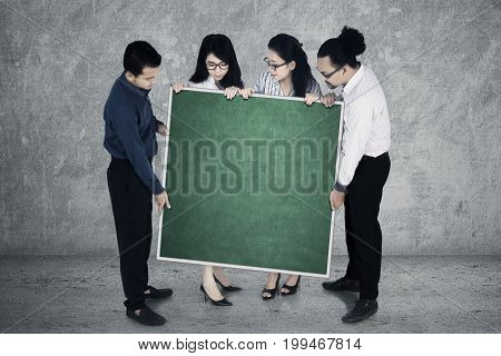 Group of young multiracial business team show empty chalkboard for advertisement