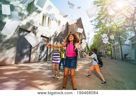Happy African girl with curly hair throws papers in the air and friends on background near school
