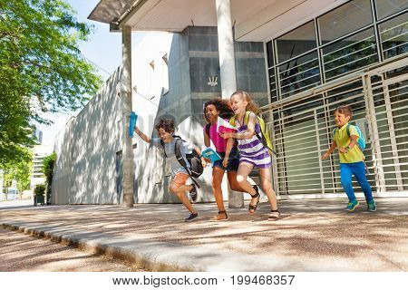 Group of happy kids boys and girls run from the  school together