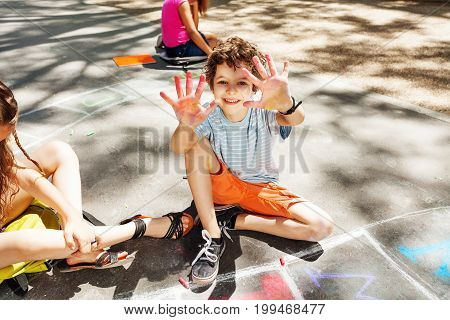 Boy shows hands to the camera  while kids draw with chalk on the road and happy handsome