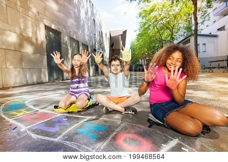 Group of kids show color palms in chalk looking at camera
