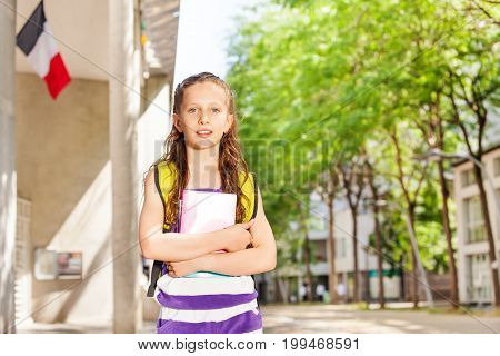 Close portrait of a girl holds textbook near the public school  with French flag