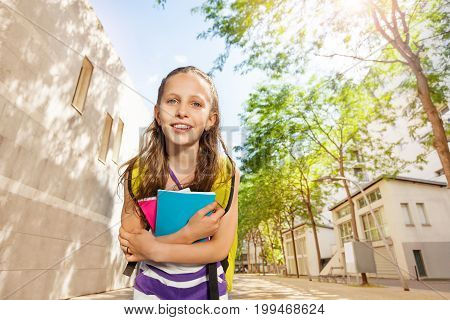 Close nice portrait of a Caucasian girl with textbooks near school