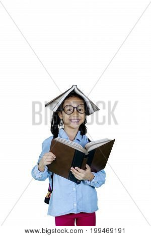 Portrait of clever little girl smiling at the camera with a book over her head isolated on white background