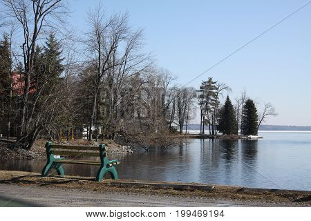 Empty bench in early spring,  on the shore of a small bay looking towards big lake