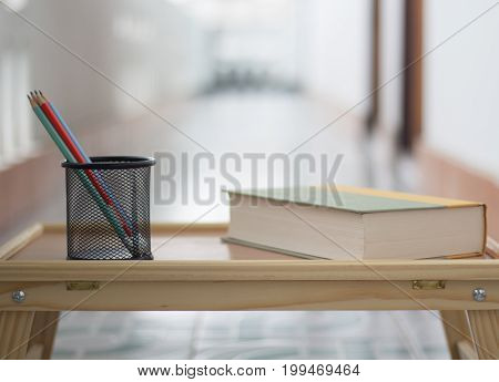Close up side view book with pencil on wooden table background.