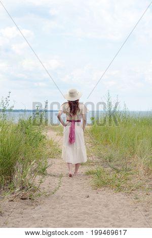 back of vintage woman walking on beach path