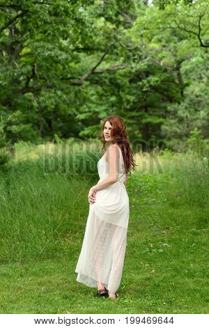 portrait of redhead woman walking on forest path