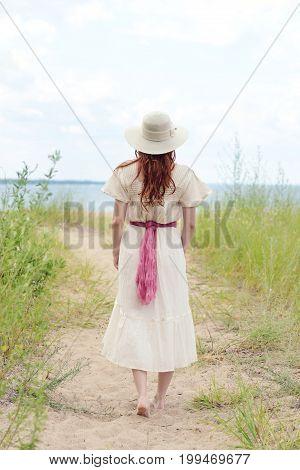 vintage woman wearing hat walking on beach path