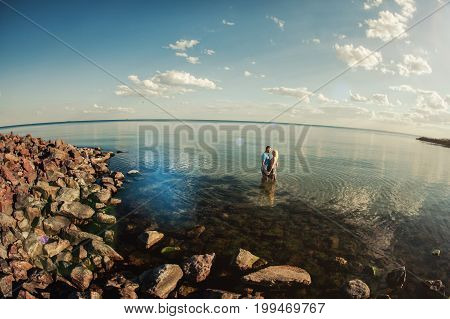 Young Loving Couple Kissing In The Sea