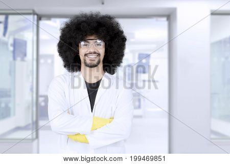Portrait of confident professional scientist wearing protective glasses and lab coat while standing with crossed arms and looking at camera