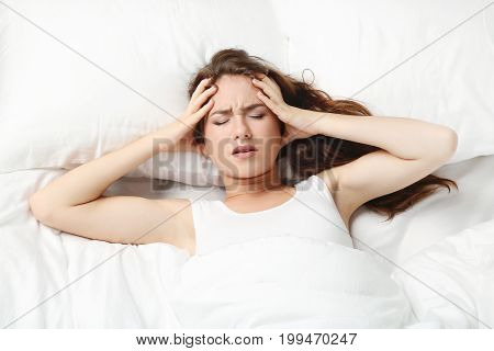 Sick Young Woman Lying In White Bed