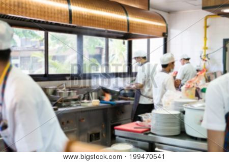 Blurry Background of inside the restaurant with the open kitchen. Chefs cooking food quickly. To prepare the served to customers.