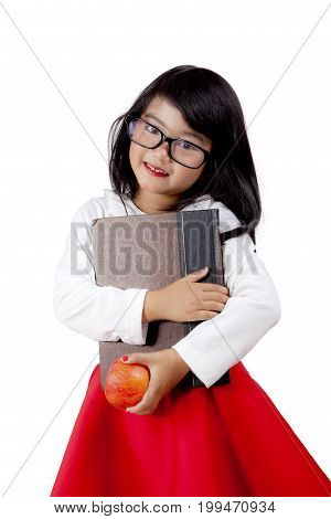 Portrait of little cute girl smiling at the camera while holding a book and an apple isolated on white background