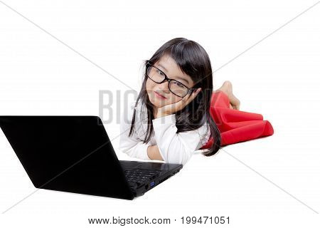 Photo of cute girl looking at the camera while lying with a laptop computer isolated on white background