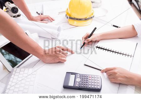 Architect and engineer discussing construction project at the working table with blueprint and equipment.