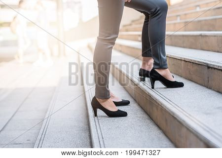 Close up shot of businesswomen colleague walking upward on the stair outdoor in city.