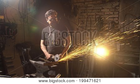 Sparks flying at the camera. Man working angular grinding machine