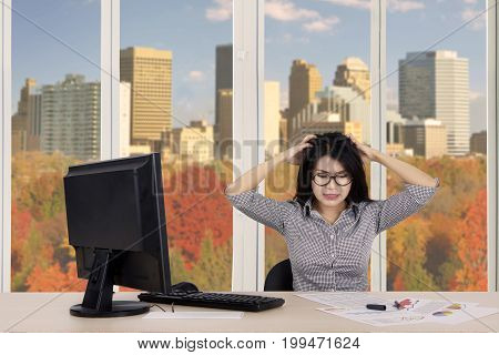 Young businesswoman looks depressed with declining graph while sitting near the window