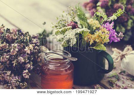 Mug of healing herbs old tea kettle honey jar and medicinal plants for healthy herbal tea. Herbal medicine. Retro toned.