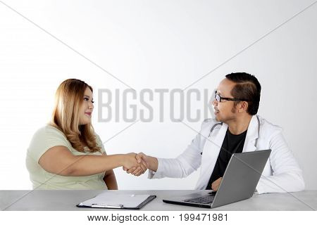 Portrait of a young doctor shaking hands with an overweight woman after check up her health