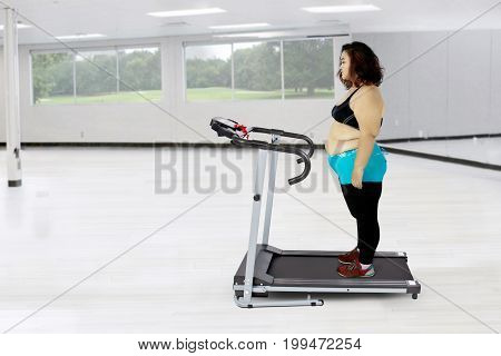 Fat woman looks doubtful while exercising with a treadmill in the fitness center