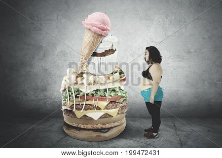 Image of fat woman wearing sportswear while hesitate to eat unhealthy food