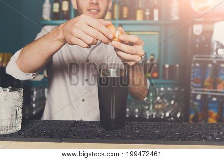 Unrecognizable bartender in bar making alcoholic cocktail with egg yolk