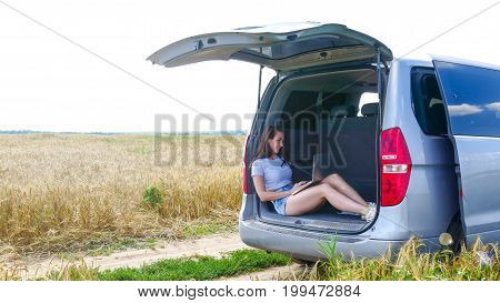 Woman sitting at the car trunk using laptop in the field