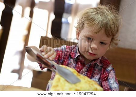 Child taking piece of pizza in restaurant