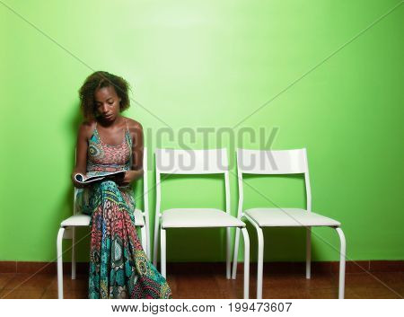 Beautiful african american woman reading magazine in waiting room of doctor