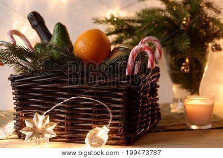 Christmas basket with oranges, champagne, candy cane and other foods against Christmas tree branches