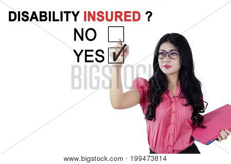 Portrait of Asian female worker using a pen while selecting a yes option with a question of disability insured on the whiteboard