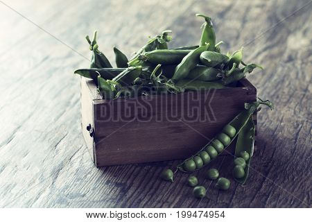 Green sweet peas in a wooden box on brown wood surface