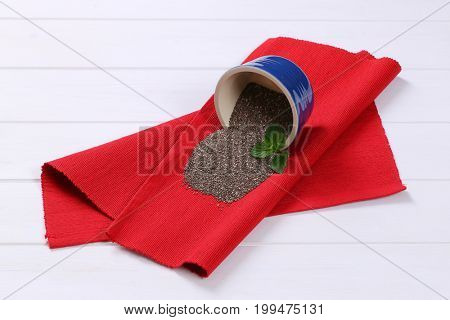 bowl of chia seeds spilt out on red place mat