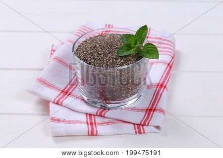 glass of chia seeds on checkered dishtowel