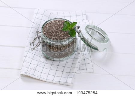 jar of chia seeds on checkered dishtowel
