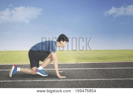 Male runner in ready position to run while kneeling in the line start on the track