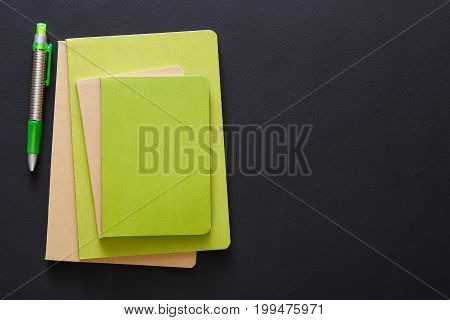 Stylish mockup with set of green notebooks and pen on black background with copy space, flat lay, concept of start-up and stationery supplies