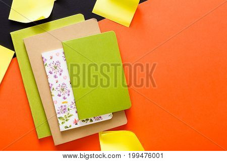 Stylish mockup with set of various colorful notebooks and memo stickers on creative multicolored work space background, copy space, flat lay, concept of start-up and stationery supplies