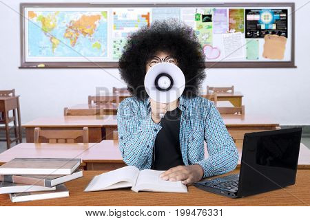 Image of a male college student shouting at the camera with a megaphone while sitting in the classroom