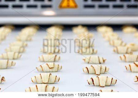 The process of producing croissants on an automatic industrial machine line. Selective focus.