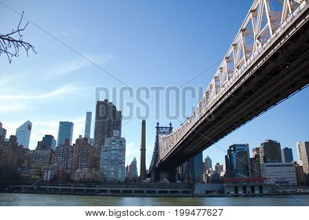 Queensboro bridge over the river and buildings in Manhattan with blue sky