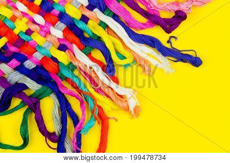Colorful rainbow stripes of threads on yellow background. Sewing and Embroidery concept