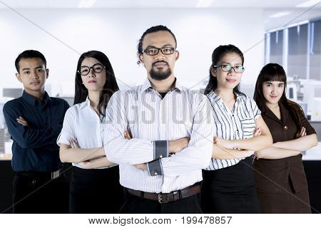 Group of multiracial businesspeople standing in the office with folded hands and looks confident